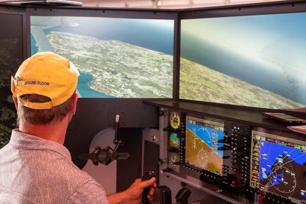 A pilot flying VFR in a Redbird flight simulator at EAA AirVenture Oshkosh 2021