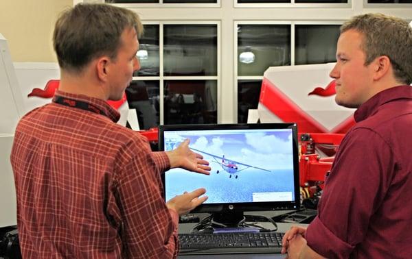 Flight instructor and student pilot debriefing a flight simulator scenario at a flight school