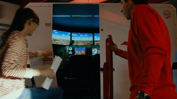 Flight instructor and student pilot entering a flight simulator for flight training